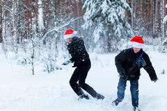 Two teenagers in Christmas hats Santa Claus having fun in the sn Royalty Free Stock Images