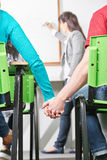 Two teenagers in class. Hold hands in class at their high school Stock Image