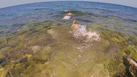 Two teenagers dive into the sea 4. The guy and the girl with a mask snorkel and fins are immersed in the sea. Boy puts flippers stock footage