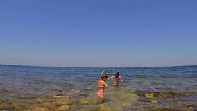 Two teenagers dive into the sea 5. The guy and the girl with a mask snorkel and fins are immersed in the sea. Boy puts flippers stock footage
