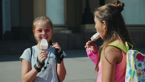 Two teenagers eat ice cream in the city square. Two teenagers with backpacks eat ice cream in the city square, laugh, talk. The camera is flying around, slow stock video footage