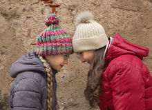 Two teenagers. Friendly confrontation, rivalry and competition concept - two teenage girls butting their heads against each other outdoor in winter clothes on Royalty Free Stock Photo
