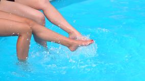 Close-up of slender legs two girls in the pool. Two teenagers girlfriends splashing around and enjoying the sun in a swimming pool whilst on vacation or holiday stock footage