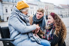 Two teenagers giving a present to a grandmother in wheelchair outdoors in winter. royalty free stock photos