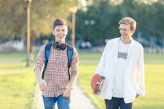 Two teenagers in a good mood with a skateboard. Rest in the park at sunset of the day Stock Photo