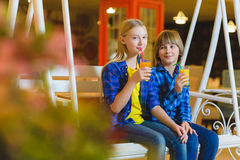 Two teenagers or happy kids - boy and girl drinking juice in cafe Stock Photography