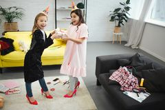 Two teenagers have fun. They stand in room and hold one gift together. Girls wear clothes and shoes for adult women