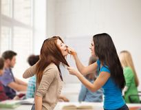 Two teenagers having a fight and getting physical. Bullying, school, education, friendship and people concept - two teenagers having a fight and getting physical Stock Image