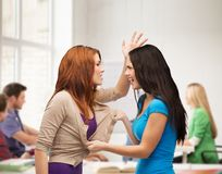 Two teenagers having a fight and getting physical. Bullying, school, education,friendship and people concept - two teenagers having a fight and getting physical Royalty Free Stock Photos