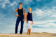 Two teenagers having fun on the beach. The sky in the background Royalty Free Stock Images