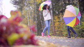 Two teenagers having fun with umbrellas in autumn park. Two teen girls playing with umbrellas in autumn park stock video footage