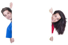 Two teenagers holding at a blank board Royalty Free Stock Image