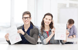 Two teenagers holding test or exam with grade A royalty free stock photos