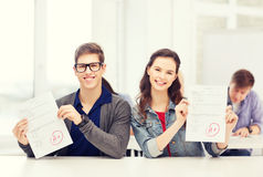 Two teenagers holding test or exam with grade A Stock Photo