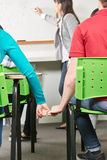 Two teenagers in love hold hands. In class Stock Photos