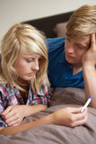 Two Teenagers Lying On Bed Stock Image