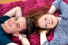 Two teenagers lying on carpet Stock Photo