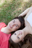 Two teenagers lying head to head on grass Stock Photo