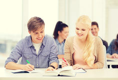 Two teenagers with notebooks and book at school Royalty Free Stock Image
