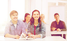 Two teenagers with notebooks and book at school Stock Photos