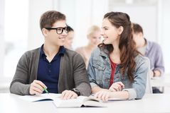 Two teenagers with notebooks and book at school Royalty Free Stock Photo