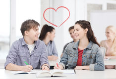 Two teenagers with notebooks and book at school Stock Images