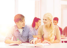 Two teenagers with notebooks and book at school royalty free stock photography