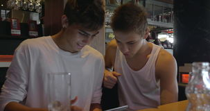 Two teenagers with pad in cafeteria. THESSALONIKI, GREECE - AUGUST 15, 2015: Two guys surfing the internet on tablet computer in cafe. Focus on illy logo, famous stock video footage
