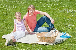Two teenagers at picnic. Teenager brother and sister enjoying a picnic in the park in a bright sunny day Royalty Free Stock Photography
