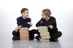 Two teenagers with piles of books Stock Photos