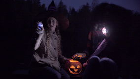Two teenagers playing with lights on Halloween night. Jack o'lantern on the bench stock footage