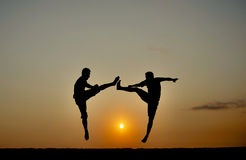 Two teenagers practices kick boxing on sunrise Royalty Free Stock Photos