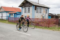 Two teenagers race on bicycles through the village past the old house royalty free stock photo