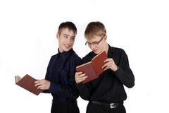 Two teenagers reading a book on white background Stock Photography
