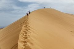 Two teenagers rise to the Dunes. Two teenagers rise to the Singing Dunes in desert national park Altyn-Emel, Kazakhstan Royalty Free Stock Photos