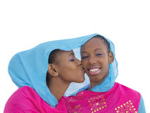 Two teenagers sharing the same veil, kiss on the cheek Royalty Free Stock Images