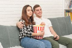 Two teenagers are sitting on the couch watching TV stock image