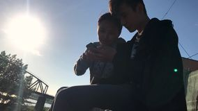 Two teenagers sitting in the street and watching funny videos on the phone. stock footage