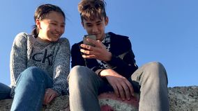 Two teenagers sitting in the street and watching funny videos on the phone. stock video footage