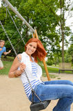 Two teenagers sitting swing in park playground Royalty Free Stock Photography