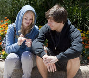 Two Teenagers Sitting and Talking. Attractive teenage couple, 18-years-old, sitting and talking on a curb with flowers behind them.  Both are wearing sweatshirts Royalty Free Stock Photos