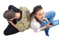 Two teenagers sitting on white with cellphones. Two teenagers on a white floor, shot from above, using cellulars, writing short messages, smiling Stock Image