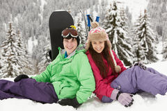Two Teenagers On Ski Holiday In Mountains. With Snowboard and Skis Stock Image