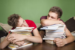 Two teenagers sleeping on books. Tired from schoolwork (laziness Stock Photography