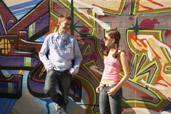 Two teenagers standing against a mural. Stock Photography