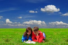 Two teenagers studying outdoors on grass Stock Photos
