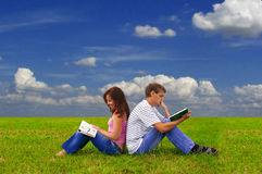 Two teenagers studying outdoors on grass Stock Photo