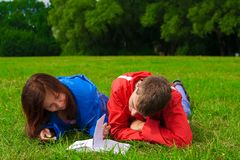 Two teenagers studying outdoors on grass Stock Image