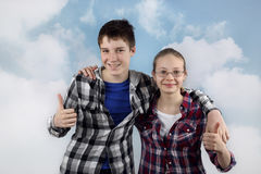 Two teenagers. Teenage relationship and friendship - Boy and girl in plaid shirts stand in embrace with happy smiles on cloudy blue sky background Stock Photo