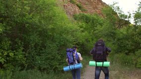 Two teenager traveling with backpacks in mountains stock video footage